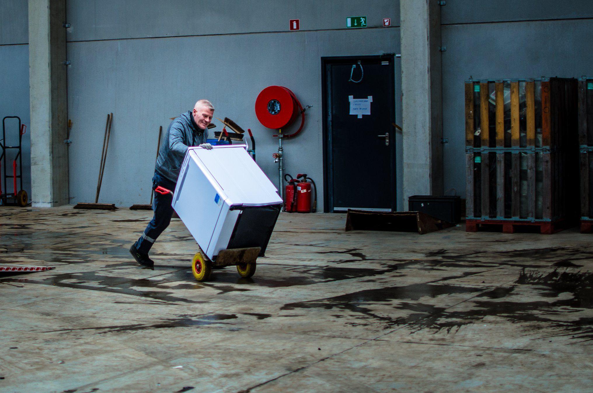 Un employé de Retrival recyclant un réfrigérateur